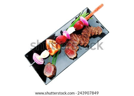 meat food : grilled fat meat served on black plate with vegetables on spit isolated on white background - stock photo