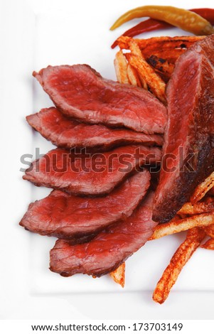 meat food : rare beef on potato chips with pepper and tomatoes over plate isolated on white background - stock photo