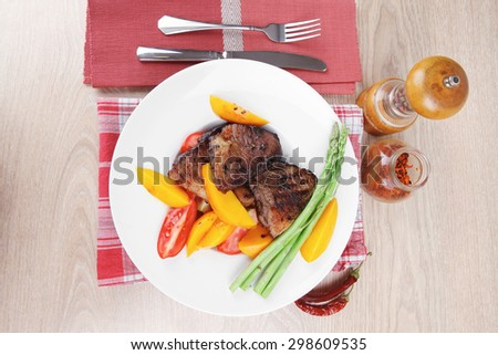 meat food : rare medium roast beef fillet with mango tomatoes and asparagus , served on white dish on red table map over wooden table - stock photo