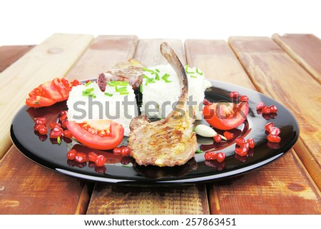 meat food: ribs on black with rice garnish and tomatoes on black on wood - stock photo