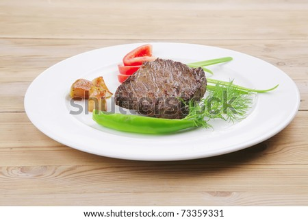 meat food : roast beef fillet mignon served on white plate with apples dill and tomatoes over wooden table - stock photo