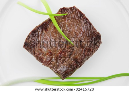 meat food : roast beef fillet mignon served on white plate with green sprouts isolated over white background - stock photo