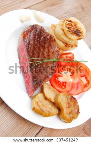 meat food : roast beef fillet mignon served on white plate with tomatoes , potatoes , and chives on wooden table - stock photo