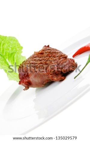 meat food : roast beef steak garnished with green lettuce and red chili hot pepper on white plate isolated over white background - stock photo