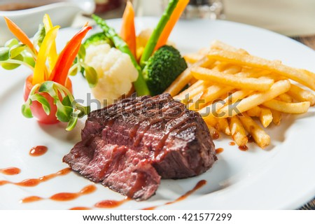 meat food : roast beef steak garnished with green lettuce and red chili hot pepper on white plate isolated    - stock photo