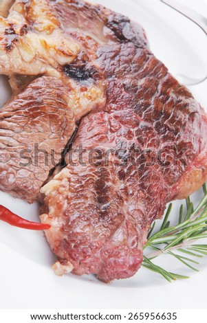 meat food : roast beef steak served on white plate with red pepper , spices , and rosemary isolated over white background - stock photo