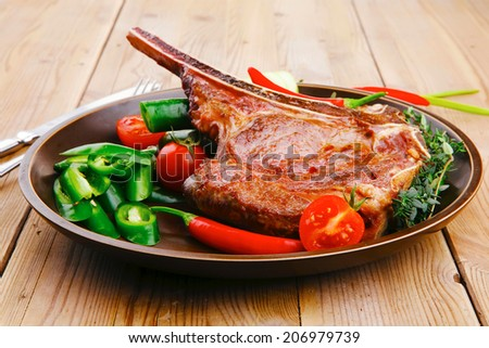 meat food : roast rib on dark dish with thyme pepper and tomato on wooden table - stock photo