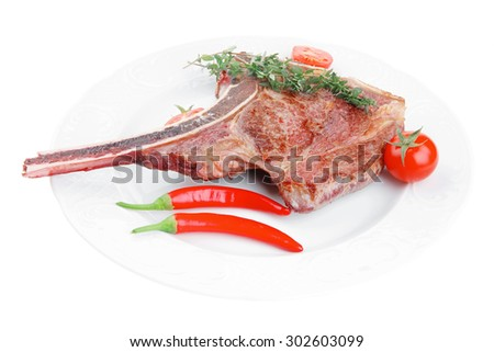 meat food : roast rib on white dish with thyme twig , pepper and tomato isolated over white background - stock photo