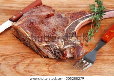 meat food : roast rib on wooden plate with thyme - stock photo