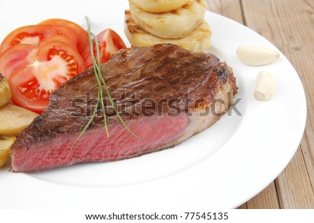 meat food : roasted fillet mignon on white plate with tomatoes and chives served on wooden table - stock photo