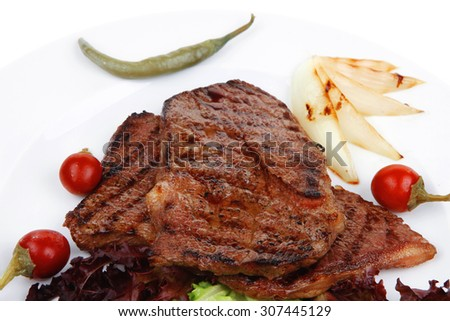 meat food : two roast steak boneless with red and chili peppers, served on green lettuce salad on dish isolated over white background - stock photo