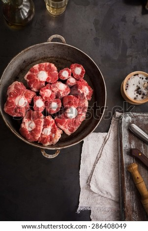 Meat for bull tail stew served on vintage metal tray over on dark blackboard. Rabo de toro food. Fresh raw oxtail cut. Top view.  Rustic style. - stock photo