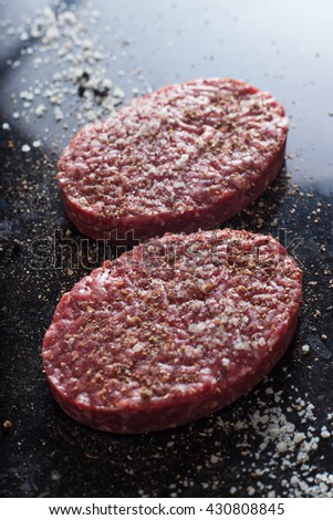 Meat for burgers, grilling, barbecue, bbq. Fresh, spicy, uncooked, delicious beef for hamburgers on dark background with copy space closeup - stock photo
