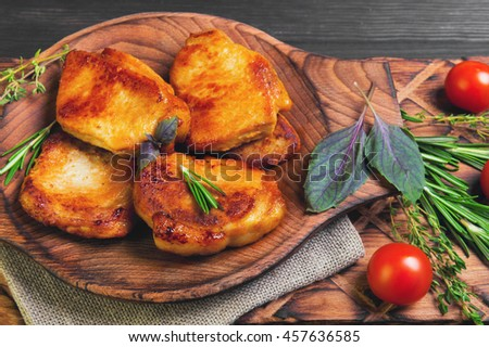 Meat fried pork steak baked, fresh green basil spices, thyme, rosemary, cherry tomatoes, burlap, brown dark wooden background in rustic style - stock photo