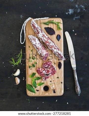 Meat gourmet snack. Salami, garlic and herbs on rustic wooden board over dark grunge backdrop, top view - stock photo