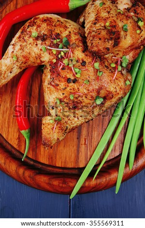 meat : grilled quarter chicken garnished with green onion pens and red peppers on wooden plate over blue wooden background - stock photo