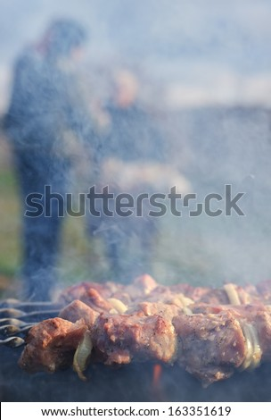 Meat grilling over a barbecue fire with smoke rising from the sizzling kebabs to cause a smoky haze with people visible in the distance cooking over a second fire - stock photo