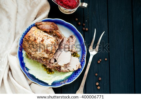 meat , home baked ham or  cold boiled pork with spices , lettuce, green peas and sweet and sour berry sauce on a wooden background - stock photo