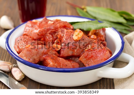 meat in marinate with garlic and bay leaf on dish on brown wooden background - stock photo