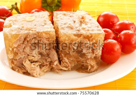 meat jelly on a plate with cherry tomatoes