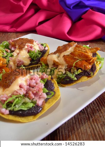 Meat mexican  tacos and quesadillas with hot sauce, nachos, jalapenos, refried beans and cheese sauce, in a mexican restaurant. Warm mexican style in the background. - stock photo
