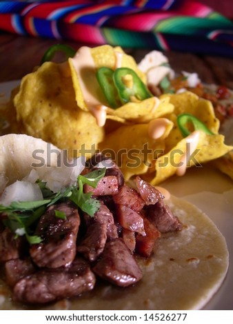 Meat mexican  tacos with hot sauce, nachos, jalapenios and cheese sauce, in a mexican restaurant. Warm mexican style in the background. - stock photo