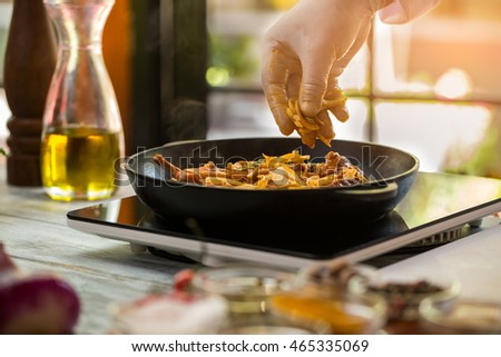 Meat on a pan. Hand holds onion pieces. Recipe of pork from chef. Preparation of meal in cafe.