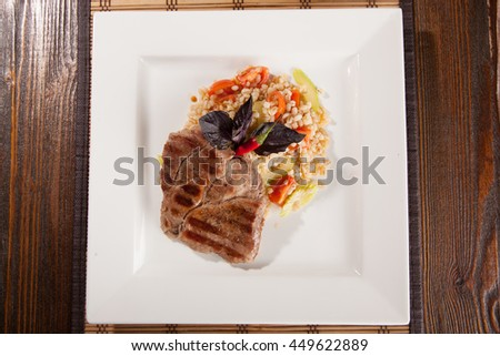 meat on a square plate with Pearl porridge on wooden table