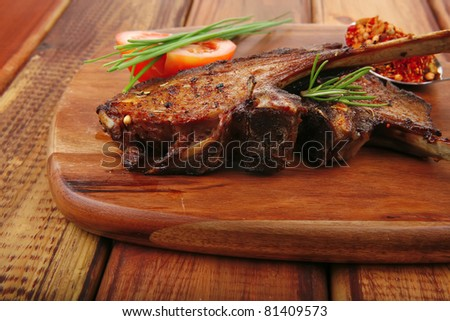 meat over wood: grilled ribs on plate with tomatoes and spices on wooden table