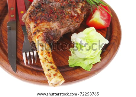 meat over wood: grilled shoulder on plate with tomatoes green lettuce and cutlery isolated on white background