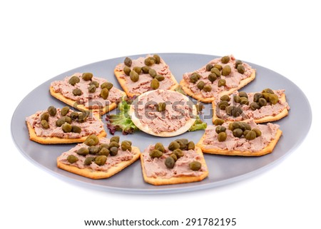 Meat pate with capers on crackers and lettuce on plate isolated on white background. - stock photo