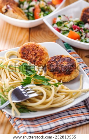 Meat patties and pasta with parsley in bowl on table. - stock photo
