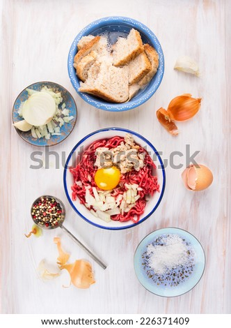 meat patties making with raw  minced meat , bun soaked , slicing onions and egg on white wooden background,top view - stock photo