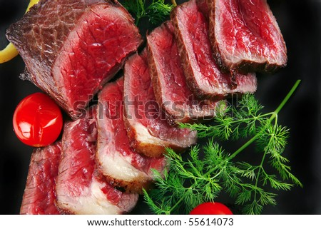 meat pepper and tomatoes on dark plate - stock photo