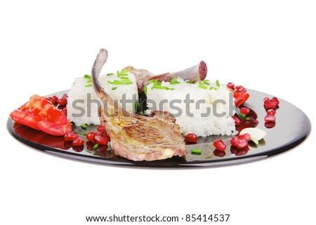 meat portion: barbecued ribs served with rice and tomatoes on black over white background