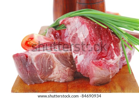 meat portion: bloody beef fillet on plate with cutlery served before cooking - stock photo