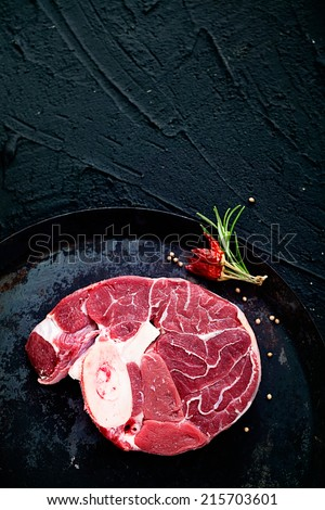 Meat. Raw meat beefsteak on  black with herbs - stock photo