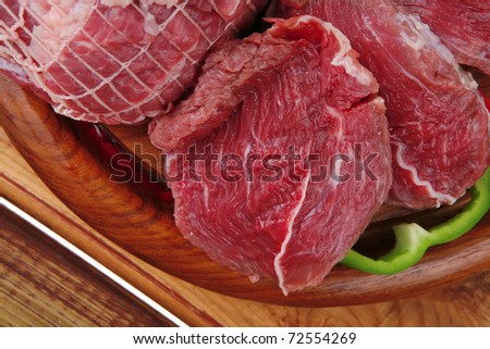 meat ready to cooking over wooden table - stock photo