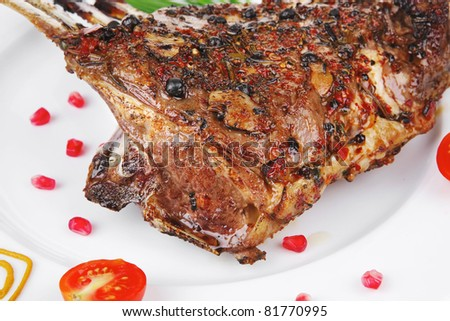 meat ribs on white plate with cherry tomatoes