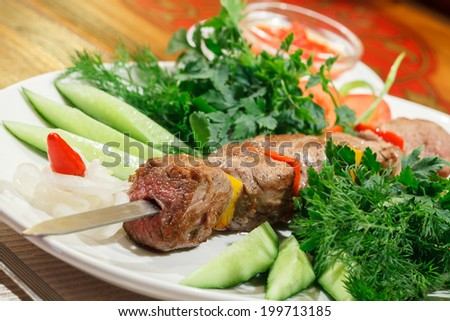 meat roasted on charcoal, served with cucumbers, tomatoes and herbs - stock photo