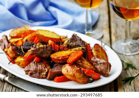 Meat roasted with potatoes, carrots, onions, rosemary and garlic. the toning. selective focus