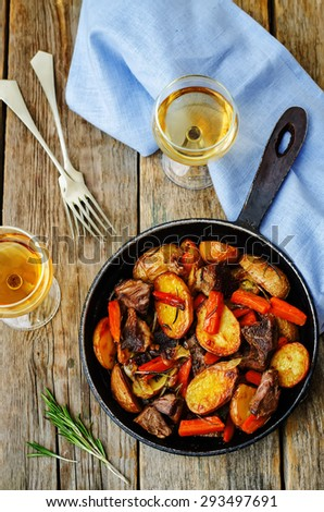 Meat roasted with potatoes, carrots, onions, rosemary and garlic. the toning. selective focus - stock photo