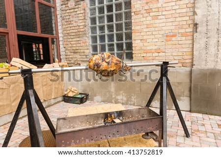 Meat roasting on a spit outdoors over an open barbecue fire on a rotating rotisserie in a courtyard - stock photo