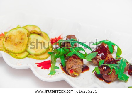 Meat rolls with zucchini and arugula on a white plate on a white background