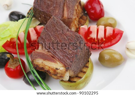 meat savory : beef fillet mignon grilled and garnished with baked apples and tomatoes on white plate isolated over white background - stock photo