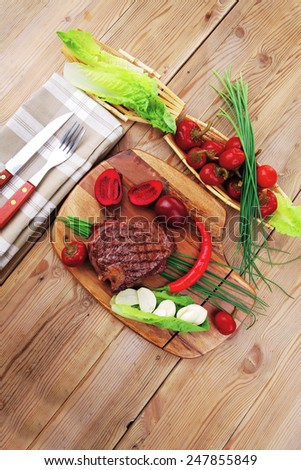 meat savory : beef grilled and garnished with green lettuce and red chili hot pepper on wooden table with cutlery - stock photo