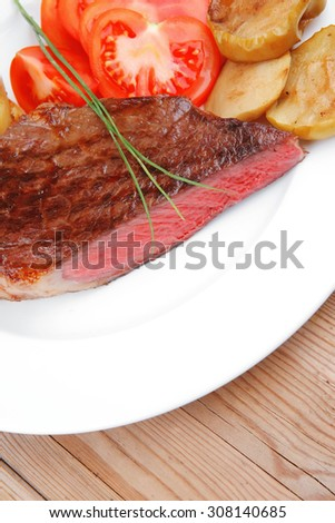 meat savory : grilled beef fillet mignon on white plate with tomatoes , potatoes and chives on wooden table - stock photo