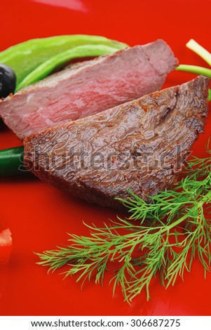 meat savory : grilled beef fillet mignon served on red plate isolated over white background with chili pepper and tomatoes - stock photo