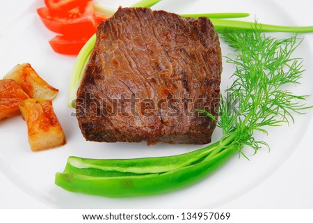 meat savory : grilled beef fillet mignon served on white plate isolated over white background with chili pepper and tomatoes