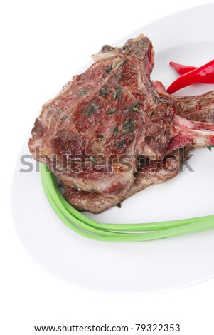 meat savory : grilled beef ribs served with green chives and raw red chili peppers on white dish isolated over white background
